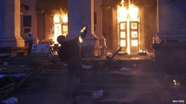 Pro-Ukraine fighter throws a molotov cocktail at the Trade Union House, Odessa. Inside dozens of Antimaidan activists were burned to death. Pic credit: Reuters