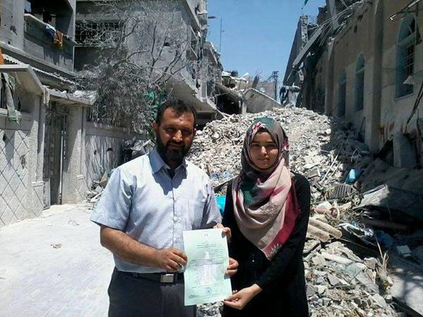 Gaza student and her dad, with her graduation certificate, outsude their destroyed home. Pic credit: Tarek Al Farra via twitter