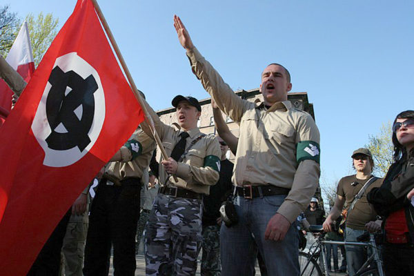 "Polish fascists give the Nazi ""sieg heil"" salute and brandish a White Power flag"